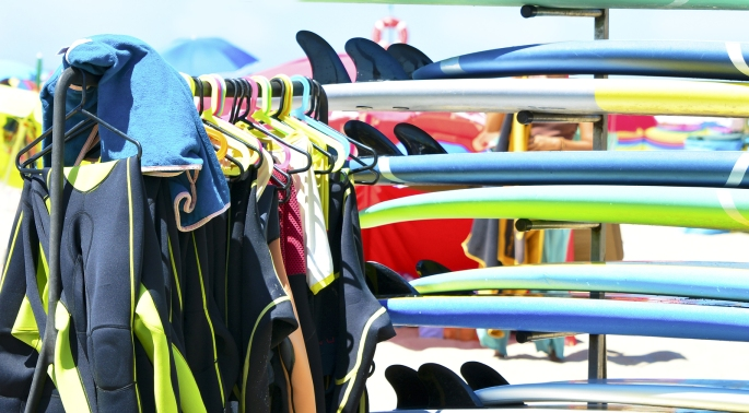 Surfboards and uniforms on the beach of Atlantic ocean at the surf school