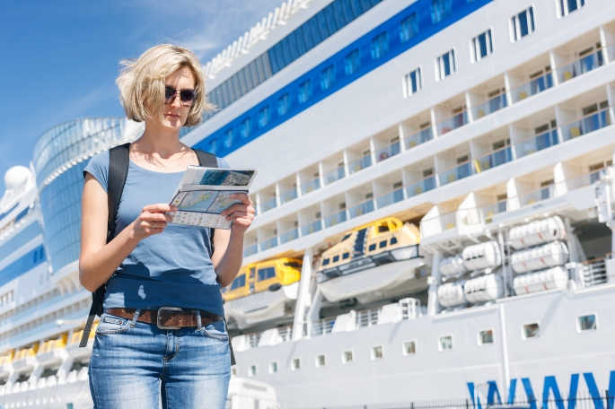 Woman with map, in front of cruise liner