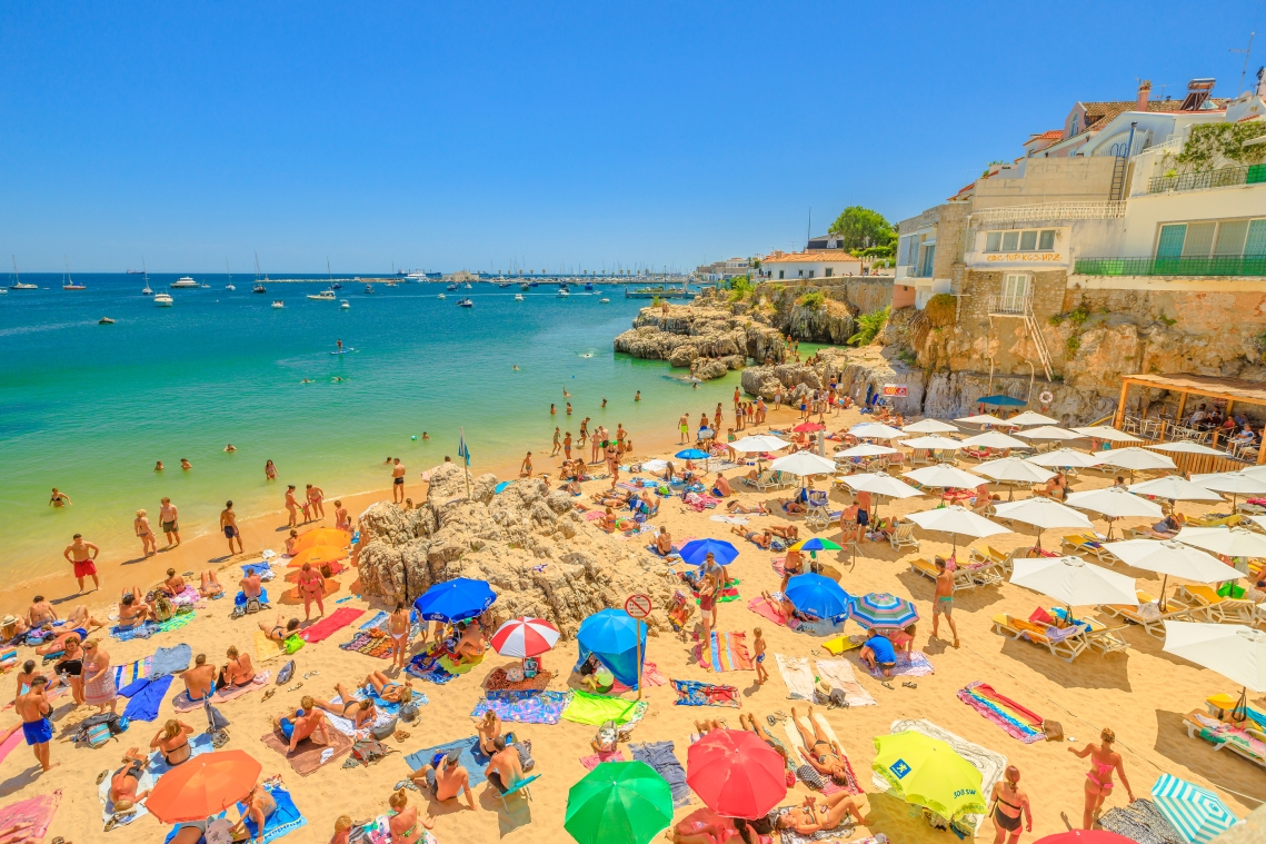Cascais, Portugal - August 6, 2017: People Sunbathing On Praia D